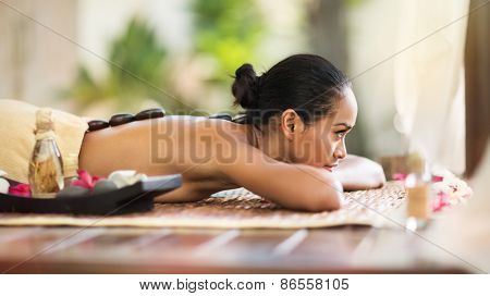 Beautiful young woman at spa outdoor, stone massage