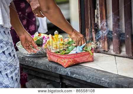 Female hands offering food to God, traditional Balinese offerings to gods in Bali with flowers and aromatic sticks