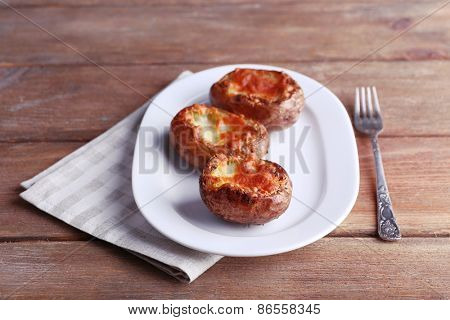 Baked potatoes on pate on wooden table