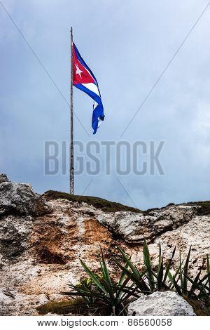 Cuban national flag on a stone hill