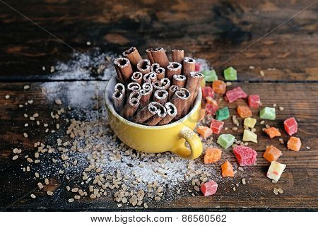 Cinnamon sticks in cup with sugar and dried fruits on wooden table background