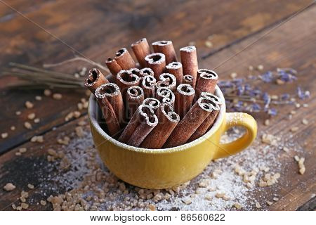 Cinnamon sticks in cup with sugar and lavender on wooden table background