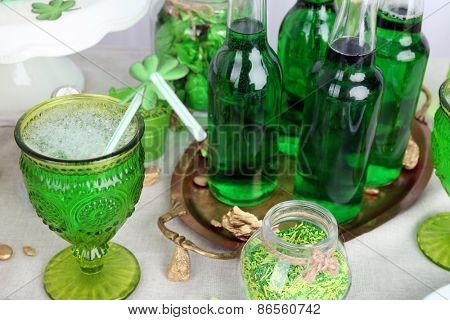 Composition for St Patrick Day with sweets and drinks on table close up