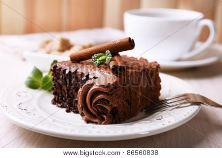 Tasty piece of chocolate cake with mint and cinnamon on wooden table and blurred planks background