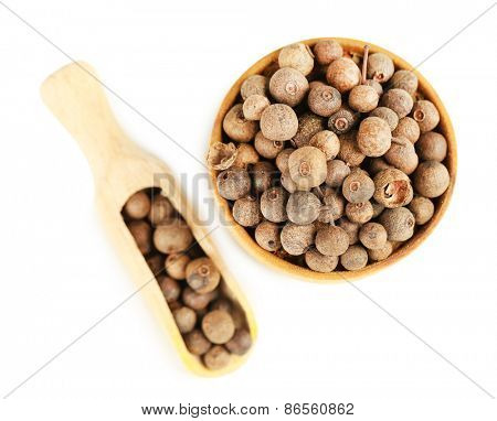 Allspice in wooden bowl, isolated on white