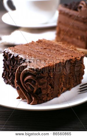 Tasty pieces of chocolate cake on wooden table background