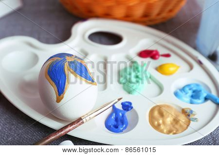 Painting Easter eggs on colorful tablecloth background