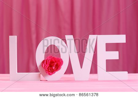 Decorative letters forming word LOVE with flower on pink background