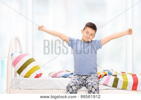 Sleepy little boy in pajamas stretching himself seated on a bed at home