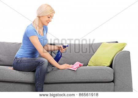 Cheerful blond woman cleaning a sofa with a rag and a cleaning spray isolated on white background