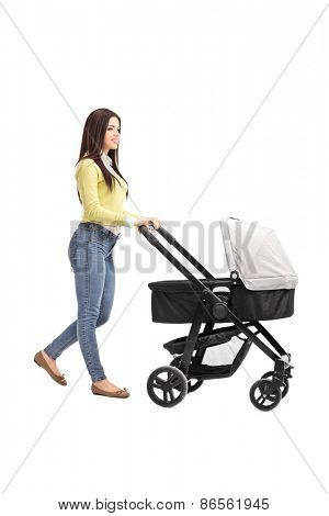 Full length profile shot of a young mother in casual clothes pushing a baby stroller isolated on white background
