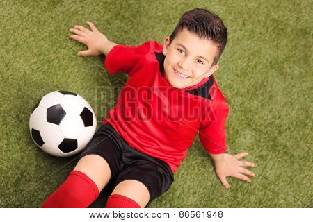 High angle shot of a junior soccer player in red jersey, sitting on a green field and looking at the camera, with a soccer ball beside him
