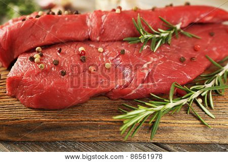 Raw beef steak with rosemary and spices on cutting board on wooden background