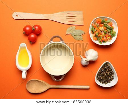 Food ingredients and kitchen utensils for cooking on orange background