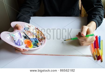 Left Hand Draws Brush With Blue Paint On Paper In Album With Several Colorful Brushes Near