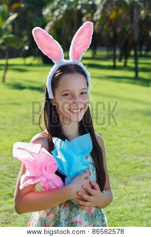 Smiling Teen Girl With Rabbit Ears Holding Easter Chocolate Eggs