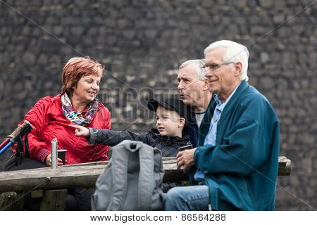 Seniors And Child On Family Trip Resting Outdoors