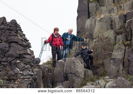 Senior Couple With Child Trekking On The Rock