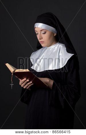 Young Beautiful Woman Nun Reading Bible Over Grey