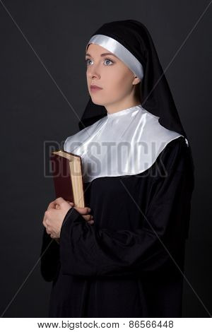 Portrait Of Young Woman Nun Holding Bible Over Grey