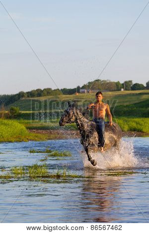 Young Man With A Naked Torso Jumps Astride A Horse Through The River
