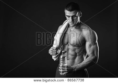 Muscular guy - bodybuilder posing on a gray background.