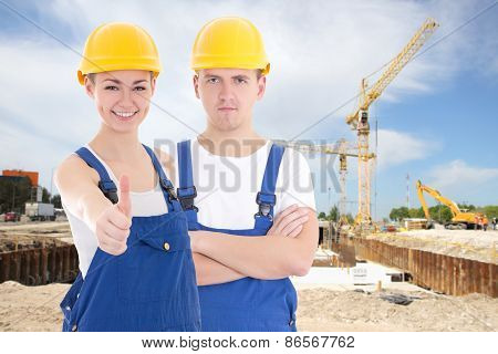 Young Man And Woman In Builder 's Uniform
