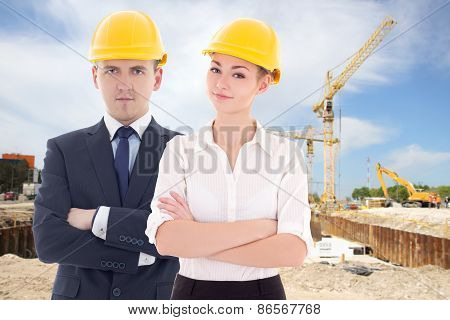 Young Man And Woman In Builder 's Helmets