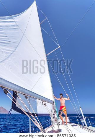 Handsome cheerful man having fun on beautiful luxury sailboat, spending summer vacation in sea cruise, enjoying freedom and recreation