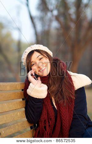 Girl Enjoying Talking On Mobile Phone On Bench In Park