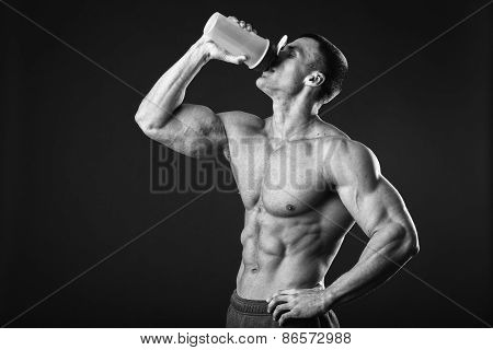 Man bodybuilder posing on gray background