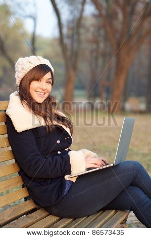 Girl Sitting With Laptop On Bench In Park
