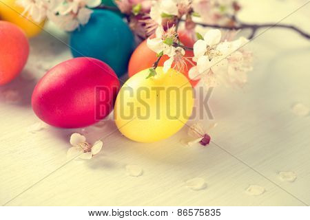 Easter. Colorful Easter eggs with spring blossom flowers over wooden background. Colored Egg Holiday border art design. Vintage toned