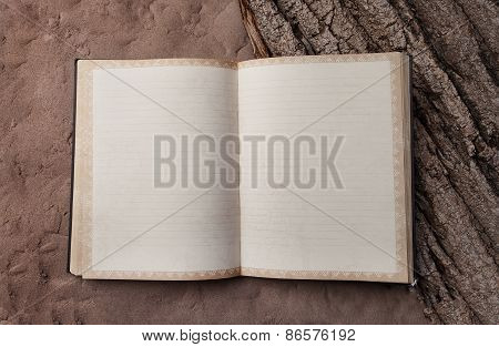 Blank Old Book In The Clear On The Sand And Tree Bark. Notebook For Records Traveler