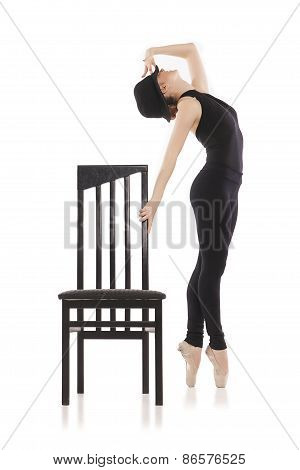 Pretty young ballerina posing with chair. Isolated on white