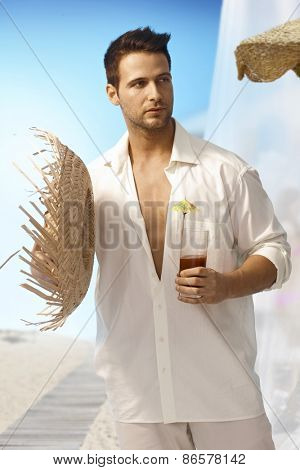 Young man holding straw hat and cocktail on summer holiday on tropical island.