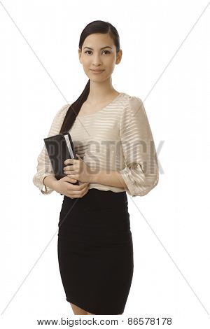 Pretty young businesswoman holding personal organizer, smiling, looking at camera.