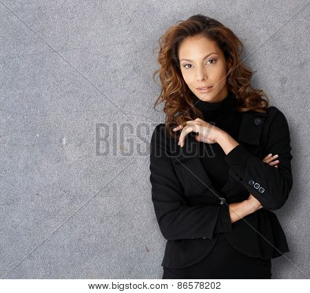 Portrait of a young successful business woman standing in front of gray concrete wall.