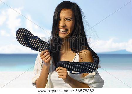 Happy Asian woman laughing on the beach at summertime, holding flip flop in hand.