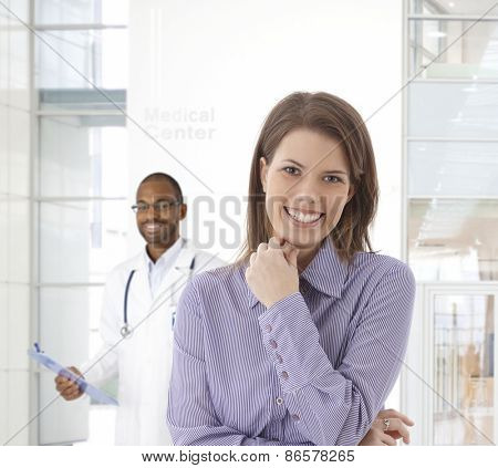 Happy young woman smiling at medical center, looking at camera, doctor standing at background.