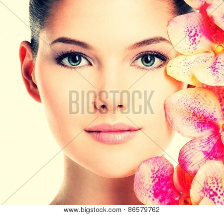 Closeup portrait of beautiful young woman with healthy skin and pink flowers near face - isolated on white.