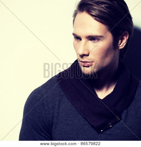 Handsome sexy man in gray pullover poses over wall with contrast shadows and looking sideways.