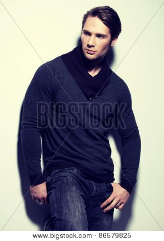 Fashion portrait of sexy handsome man in gray pullover poses over wall with contrast shadows and looking sideways.