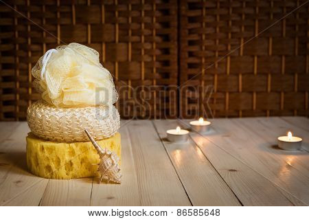 Three sponges and sea shell, candles on background