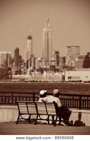 Old couple sit at waterfront with Manhattan city view