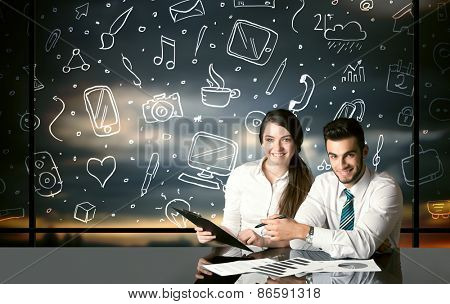 Business couple sitting at table with hand drawn social media icons and symbols