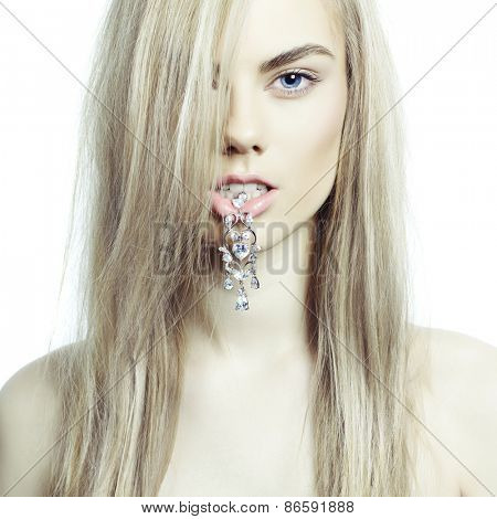 Fashion portrait of young beautiful lady with an earring in her mouth