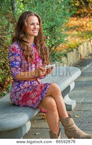 Happy Young Woman Writing Sms While Sitting On Bench In City Par