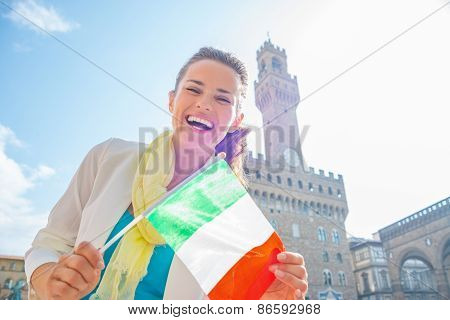 Happy Young Woman Showing Flag In Front Of Palazzo Vecchio In Florence, Italy