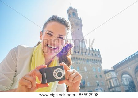 Happy Young Woman With Photo Camera In Front Of Palazzo Vecchio